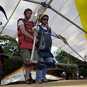 A tandem hang glider passenger receives instructions from the pilot before take off from the hillside of Pedro Bonita high in the hills of Rio de Janeiro. Pilots of hang gliders and para gliders take tourists for tandem flights with breathtaking views of the city before landing on Sao Conrado beach. Rio de Janeiro,  Brazil. 9th September 2010. Photo Tim Clayton