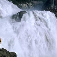 A hiker walks beside Virginia Falls on the Nahanni River, Northwest Territories, Canada.
