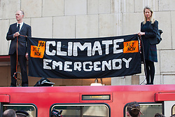 London, UK. 17th April 2019. Climate change activists from Extinction Rebellion glue themselves to a DLR train at Canary Wharf station on the third day of International Rebellion activities to call on the British government to take urgent action to combat climate change.