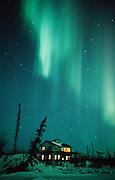 Alaska. Aurora Borealis light up the night sky above a house with lit windows.