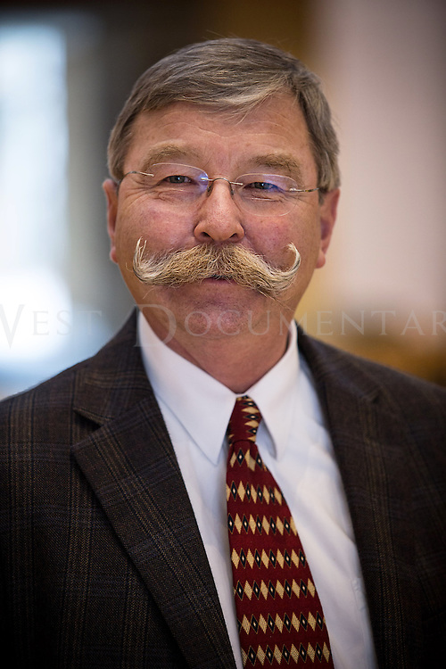 """Jim Shamp, director of public relations for the North Carolina Biotechnology Center, which is located within Research Triangle Park (RTP), poses for a portrait on March 19. Shamp has been growing a mustache for over 50 years and has been growing the very characteristic """"handlebar mustache"""" for the last 10. Shamp stated that a little over 10 years ago he was cleaning some brush up from his yard after a storm and one of the tree limbs smack him across the face where his mustache was. The swipe of the tree branch left what appeared to be a Nike swooshes on his mustache and when he arrived back inside of his house his wife stated that she liked the look and he has been with the style ever since. Shamp uses all-natural beeswax from Oregon to finish off and style the ends to his unique """"stache""""."""