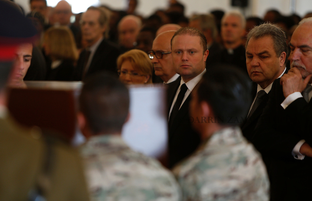 Malta's Prime Minister Joseph Muscat (3rd R) watches as Armed Forces of Malta soldiers lay down coffins with the bodies of 24 migrants during an inter-faith burial service at Mater Dei Hospital in Tal-Qroqq, outside Valletta, April 23, 2015. European Union leaders who decided last year to halt the rescue of migrants trying to cross the Mediterranean will reverse their decision on Thursday at a summit hastily convened after nearly 2,000 people died at sea.  Public outrage over the deaths peaked this week after up to 900 migrants died last Sunday when their boat sank on its way to Europe from Libya.<br /> REUTERS/Darrin Zammit Lupi MALTA OUT. NO COMMERCIAL OR EDITORIAL SALES IN MALTA
