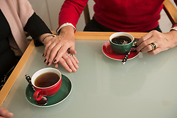 Hands of two senior woman comfort each other coffee on table, Munich, Bavaria, Germany
