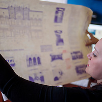 El Morro Theatre manager Jennifer Lazarz looks over historic blueprints of the theater at her office Thursday.
