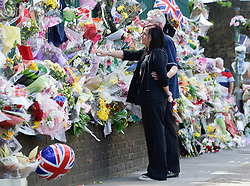 © London News Pictures. 26/05/2013. Woolwich, UK.  Sara McClure (sister of Lee Rigby) and  Ian Rigby (stepfather) looking at flowers left at the scene of his death. Family of murdered serviceman Drummer Lee Rigby visit the scene of his death in Woolwick, London. Drummer Lee Rigby was murdered by two men in Woolwich town centre in what is being described as a terrorist attack. Photo credit: Ben Cawthra/LNP