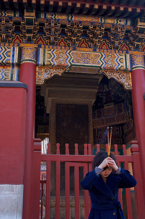 A woman prays at Yonghegong.  This Tibetan Temple is known to tourists as Lama Temple and it's located in Dongcheng District Beijing, China. This is the largest Temple of its kind outside of Tibet.  In 1723 the structure was turned into a Temple after the resident became the third Qing Emperor.
