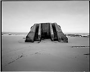 THE ATLANTIC WALL. .pic shows: A FALLEN OBSERVATION POST ON THE BEACH AT WISSANT BETWEEN CALIAS AND BOULGNE..WORLD WAR TWO ENDED IN EUROPE IN MAY 1945, THIS YEAR SEES THE 60th ANNIVERSARY OF THAT VICTORY..THE ATLANTIC WALL BUILT BY GERMANY IN WORLD WAR 2 STRETCHED FROM NORWAY VIA DENMARK, HOLLAND, BELGIUM AND FRANCE TO THE SPANISH BORDER. THE MAIN CONCENTRATION OF BUNKERS,BLOCKHOUSES AND DEFENCES WERE ALONG THE DUTCH, BELGIAN AND FRENCH COASTAL AREAS MOST UNDER THREAT FROM AN ALLIED INVASION. THE CONSTRUCTION OF THE WALL BEGAN IN 1942 AND CONTINUED UP UNTIL THE JUNE 6th ALLIED INVASION ON D-DAY IN 1944..TENS OF THOUSANDS OF WORKERS AND PRISONERS FROM THE GERMAN OCCUPIED AREAS OF EUROPE WERE EMPLOYED BY THE ORGANISATION TODT NAMED AFTER FRITZ TODT, THE GERMAN ENGINEER WHO DIED IN 1942 (TO BE SUCEEDED BY ALBERT SPEER) IN THE BUILDING WORK. BETWEEN THE RIVERS LOIRE AND DIVES 87,257 WORKERS WERE USED INCLUDING 55,000 FRENCHMEN, 11,500 GERMANS, 4,200 DUTCH, 6.600 BELGIANS, 2,600 NORTH AFRICANS AND SEVERAL THOUSAND FROM EASTERN EUROPE..THE ATLANTIC WALL WAS THE LARGEST BUILDING PROJECT SINCE THE ROMAN EMPIRE. MANY OF THE COLOSSAL GUN BUNKERS AND UNDERGROUND DEFENSIVE CHAMBERS REMAIN. SOME HAVE FALLEN FROM CLIFF TOP POSITIONS WHILE OTHERS ARE PARTLY CONSUMED BY SAND DUNES. THE RAVAGES OF WAR, TEN THOUSAND TON BOMBS AND 60 YEARS OF COASTAL WEATHER HAVE HARDLY AFFECTED THESE LEVIATHAN LIKE STRUCTURES WHICH LOOK LIKELY TO LAST AS LONG AS THE RUINS OF ANCIENT ROME. A FITTING REMINDER OF A WORLD THAT COULD HAVE BEEN FROM 60 YEARS AGO..COPYRIGHT PHOTOGRAPH BY BRIAN HARRIS  © 2005.07808-579804