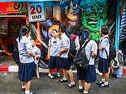 24 NOVEMBER 2015 - BANGKOK, THAILAND:  Thai school girls wait to go into a haunted house at the Wat Saket temple fair. Wat Saket is on a man-made hill in the historic section of Bangkok. The temple has golden spire that is 260 feet high which was the highest point in Bangkok for more than 100 years. The temple construction began in the 1800s in the reign of King Rama III and was completed in the reign of King Rama IV. The annual temple fair is held on the 12th lunar month, for nine days around the November full moon. During the fair a red cloth (reminiscent of a monk's robe) is placed around the Golden Mount while the temple grounds hosts Thai traditional theatre, food stalls and traditional shows.       PHOTO BY JACK KURTZ