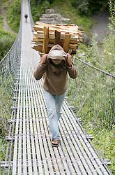 THEMENBILD - Trekkingtour in Nepal um die Annapurna Gebirgskette im Himalaya Gebirge. Das Bild wurde im Zuge einer 210 Kilometer langen Wanderung im Annapurna Gebiet zwischen 01. September 2012 und 15. September 2012 aufgenommen. im Bild nepalesische Träger tragen Holz über eine Hängebrücke // THEME IMAGE FEATURE - Trekking in Nepal around Annapurna massif at himalaya mountain range. The image was taken between september 1. 2012 and september 15. 2012. Picture shows nepalese Porters carrying wood over a swing bridge, NEP, EXPA Pictures © 2012, PhotoCredit: EXPA/ M. Gruber