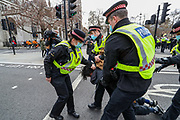 A female police officer of the city of London forcefully pulls the hair of a restrained demonstrator during clashes following a 'Kill the Bill' protest outside the Houses of Parliament in London on Saturday, April 3, 2021. The demonstration is against the contentious Police, Crime, Sentencing and Courts Bill, which is currently going through Parliament and would give police stronger powers to restrict protests. (Photo/ Vudi Xhymshiti)