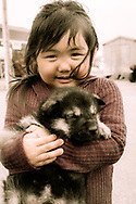 Dogs are part of the inuit culture. That little girl is taking of the puppy.