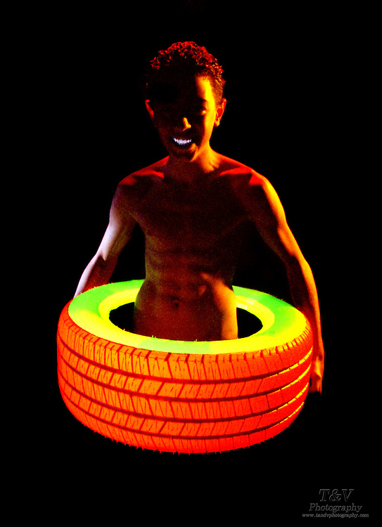 Young Boy with a flying glowing tire.Black light