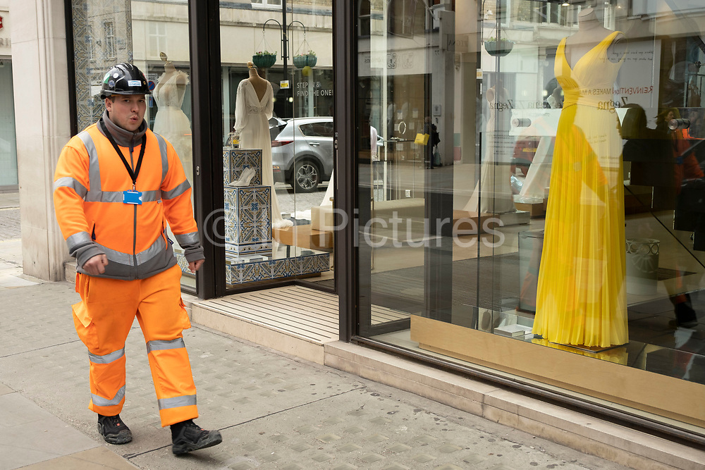 Workman in orange high viz overalls passes a shop window with a yellow dress on a mannequin on Bond Street on 25th May 2021 in London, United Kingdom. These high end brands are seen next to each other on a very ordinary wall. Bond Street is one of the principal streets in the West End shopping district and is very upmarket. It has been a fashionable shopping street since the 18th century. The rich and wealthy shop here mostly for high end fashion and jewellery.