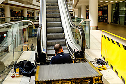 A maintenance worker repairing an escalator in Eastgate Shopping Mall in Basildon, Essex.