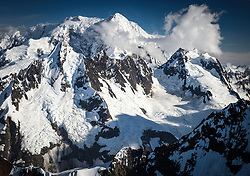 Mount Crillon (12,726 ft.) rises above the clouds near the Johns Hopkins Glacier in Glacier in Glacier Bay National Park and Preserve.<br /> <br /> Glacier Bay National Park is located in southeast Alaska. Known for its spectacular tidewater glaciers, icefields, and tall costal mountains, the park is also an important marine wilderness area. The park a popular destination for cruise ships, is also known for its sea kayaking and wildlife viewing opportunities. <br /> <br /> Glacier Bay National Park is home to humpback whales which feed in the park's protected waters during the summer, both black and grizzly bears, moose, wolves, sea otters, harbor seals, steller's sea lions and numerous species of sea birds. <br /> <br /> The dynamically changing park, known for its large, contiguous, intact ecosystems, is a United Nations biosphere reserve and a UNESCO World Heritage site.