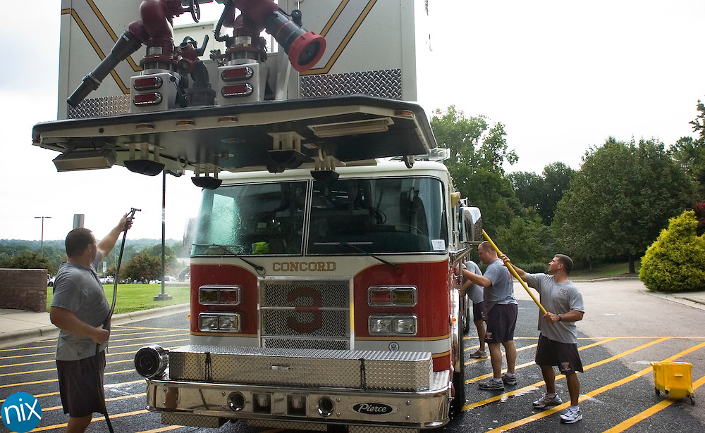 Concord Firefighters Galen Shumaker, at left with hose, Lee Cavin, with brush, Ben Klauder, Clint Little and Brent Seagraves wash their ladder truck Thursday morning. Concord currently has two ladder trucks and has received a grant for another.