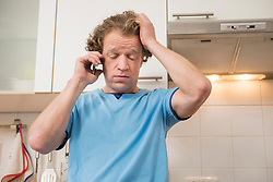 Serious man on cell phone in kitchen