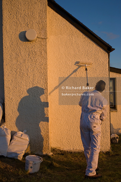 Warm evening sunshine casts shadow of painter and decorator on hilltop cottage wall in hamlet of Hallin, Waternish, Skye