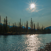 A photographer frames a scene beside the Bow River in Banff National Park, Alberta, Canada.