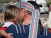 Jan 31, 2009 -- PHOENIX, AZ: A man kisses his daughter while traditional Nahuat (Aztec) dancers perform a blessing at the Macehualli Work Center. The Macehualli Work Center in north Phoenix opened six years as a city of Phoenix supported day labor center. The work center is now privately owned but still supports day laborers who congregate in the area. Many of the center's clients are undocumented immigrants. The presence of the undocumented immigrants has made the center a flashpoint in the illegal immigration debate in Phoenix.  Photo by Jack Kurtz / ZUMA Press