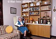 Active Aging Senior Citizens, Retired, Activities, Elderly Reads in Chair next to Memorabilia