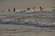 Early morning on a part of China beach in Danang. The light from the sun highlights the top of the waves. In the background, people are having a bath.