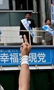 Some gives Hisshou Yanai the middle finger while he is campaigning for the Happiness Realisation Party in Shinjuku, Tokyo, Japan Friday, May 28th 2010