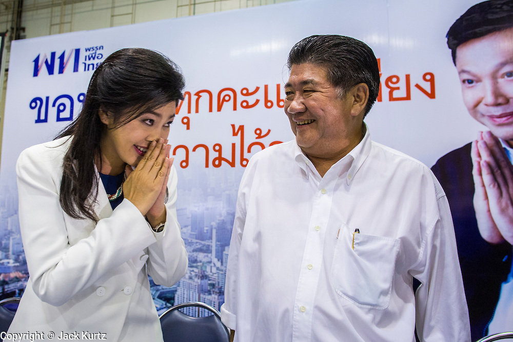 """03 MARCH 2013 - BANGKOK, THAILAND: <br /> YINGLUCK SHINAWATRA, the Thai Prime Minister, (left) """"wais"""" (formal Thai greeting) other members of the Pheu Thai party leadership after announcing that Pongsapat Pongchareon (whose photo is on the billboard in the background) lost the Bangkok Governor's election. Pongsapat Pongchareon, running on the Pheu Thai ticket, lost the Bangkok's Governor's race to MR Sukhumbhand Paribatra, the incumbent running on the Democrat ticket. Sukhumbhand won the race after scoring a record number of votes, more than 1.2 million to Pongsapat's 1 million. The results were seen as an upset even though Sukhumbhand was the incumbent because all of the pre-election polls and the exit polls conducted on election day showed Patsapong winning.     PHOTO BY JACK KURTZ"""