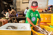 17 JUNE 2013 - YANGON, MYANMAR:  A man packs fish into a box of ice in a large Yangon fish market. The market serves both domestic retail customers and wholesale international customers. With thousands of miles of riverine waterways and ocean coastline Myanmar has a large seafood and fishing industry.     PHOTO BY JACK KURTZ