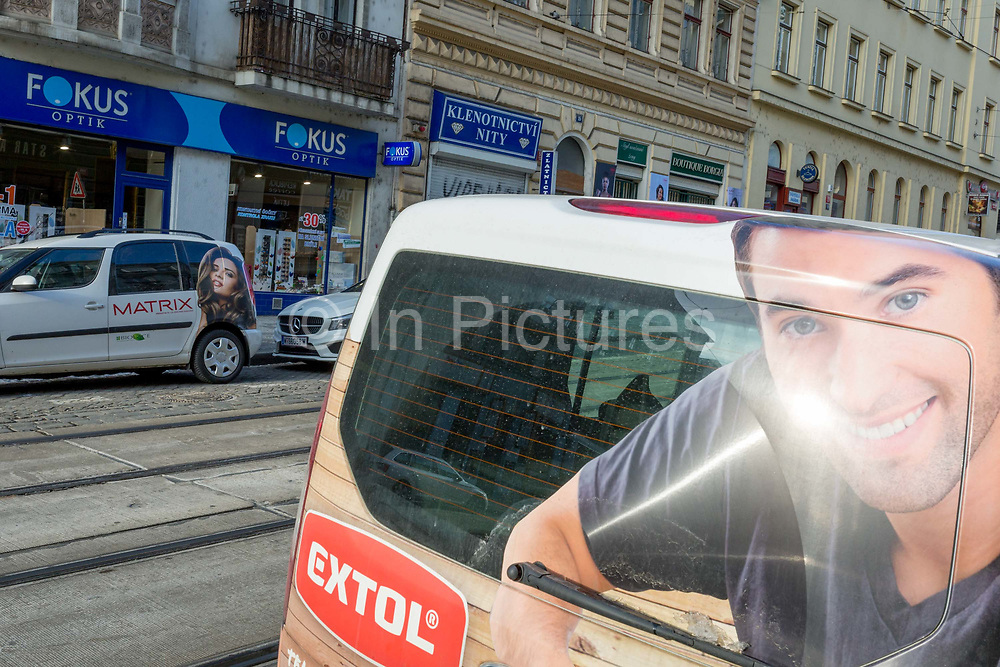 The faces of a man and a woman appear on the sides of two vans on Milady Horakove street, Holesovice district, Prague 7, on 20th March, 2018, in Prague, the Czech Republic.
