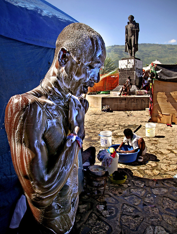 At Champ de Mars camp in downtown Port-au-Prince residents deal with  the temporary living conditions that are taking on aspects of permanency. teaming with dwellers in this shanty town on May 26, 2010. .Moise bathes under the towering statue of the forefather of Haitian Independence Toussaint Louverture..***For Fred Grimm package for July 11***