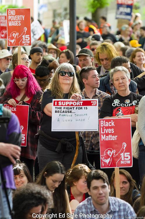 A crowd composed of protestors with signs listens to a speaker at a 2015 May Day rally in Portland, Oregon.