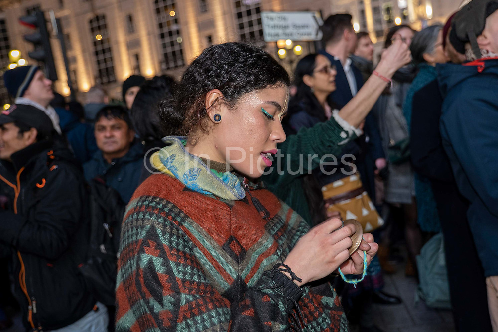 A female with small hand cymbals celebrates during a Hare Krishna street dance on New Years Eve at Piccadilly on the 31st December 2019 in London in the United Kingdom.