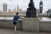 A runner stretches his joints overlooking the Houses of Parliament across the river Thames in Westminster, on 27th March 2019, in London, England