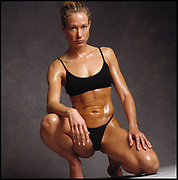 Portrait of an oiled up beautiful woman bodybuilder in exercise attire kneeling on gray background and flexing abdomen..