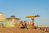 Life guard on the beach holding up a surf board as they walk between sunbathers