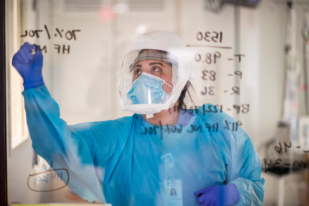 A nurse writes on a patient's room window in the COVID-19 Intensive Care Unit at Salinas Valley Memorial Hospital in Salinas, Calif. on Jan. 26, 2021.