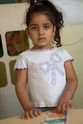 Nursery School girl doing a jigsaw,