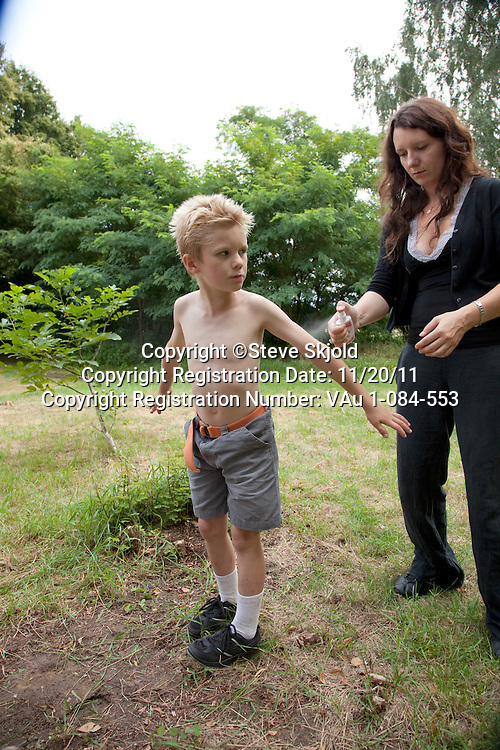 Boy age 8 being sprayed with mosquito repellent by his mother age 8 and 32. Zawady Central Poland