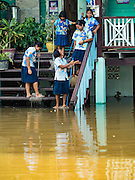 30 SEPTEMBER 2016 - SAI NOI, AYUTTHAYA, THAILAND: Girls at Wat Boonkannawas School clean up the flood waters that have inundated the school. The Chao Phraya River, the largest river that runs through central Thailand, has hit flood stage in several areas in Ayutthaya and Ang Thong provinces. Villages along the river are flooded and farms are losing their crops due to the flood. This is the same area that was devastated by floods in 2011, but the floods this year are not expected to be as severe. The floods are being fed by water released from upstream dams. The water is being released to make room for heavy rains expected in October.      PHOTO BY JACK KURTZ