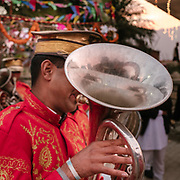 A musician from the band following the wedding party across town. He is playing tuba.