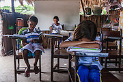 Rogerio Brito (left), 9, Adriel Brito (center), 13 and Luziulene Brito, (right), 9, during a school lesson. They are taught by their family member Joina Brito in a shack built to serve as a school. In Queimada dos Britos lives around 60 people.  In the oasis everybody is a relative, cousins intermarrying frequently as a normal course. The legend says that the founder Manuel Brito, when running away from home due to a drought that was scorching his homeland, he ended up settling down in the only non-sandy portion of the Lençois.