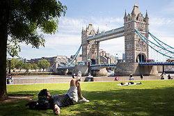 © Licensed to London News Pictures. 02/06/2021. London, UK. A man relaxes during sunny weather in Potters Fields Park in Central London. Temperatures are expected to rise with highs of 28 degrees forecasted for parts of London and South East England today . Photo credit: George Cracknell Wright/LNP
