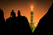 A couple relaxes as they watch the beautiful Taipei City skyline and Taipei 101.