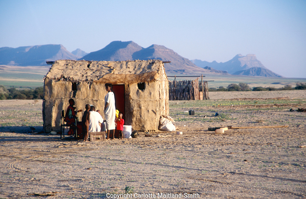 House in Purros village in Kaokoveld region north west Namibia Africa The Herero's dress, consisting of several layers and, once married, a 'cow horn' head dress, derives from Victorian-era German missionaries who took exception to what they considered a lack of modesty among the local women..