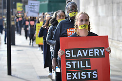 "© Licensed to London News Pictures. 14/10/2107. London, UK. People take part in the ""The Walk For Freedom"", marching around the capital demonstrating against modern slavery.  The protest is co-ordinated with other walks which abolitionist group A21 is staging in 400 cities around the world on the same day. The facemasks represents the silence of modern slaves. Photo credit : Stephen Chung/LNP"