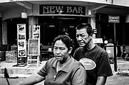Two people on a motorbike drive past a bar advertising free wifi in Chiang Mai, Thailand. (November 23, 2011)