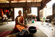 A monk cleans his bowl after eating his lunch. It's just about midday. One of the 227 Buddhist precepts a monk must adhere (vinaya) prohibit monks to eat food after noon.