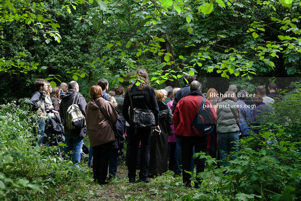 Visitors stand in woodland to listen to a speaker give a talk during a tour of Nunhead Cemetery whose deceased occupants were important members of Victorian society from the industrial age. During this annual open day, it is an opportunity for the Friends of the cemetery to celebrate and educate Londoners, old and young - thereby helping to preserve and conserve this historic site.