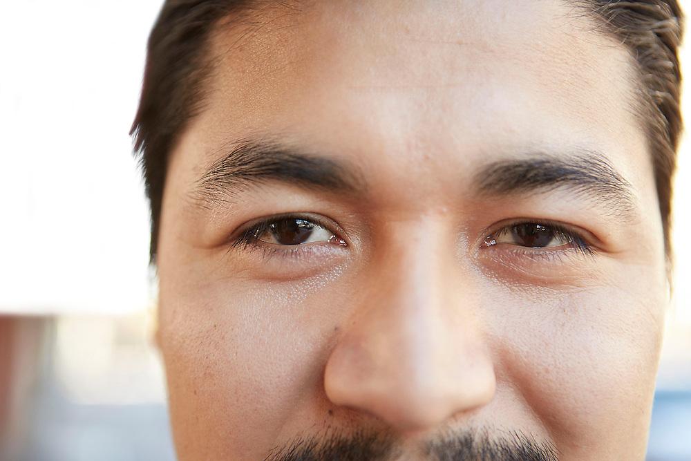 Close up smiling eyes portrait photograph of Hispanic male